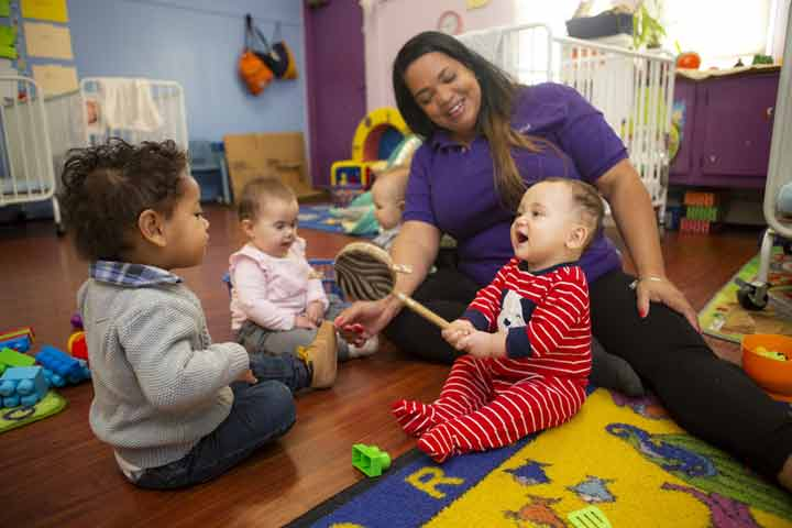 Teacher with infant and toddler engaged in play.