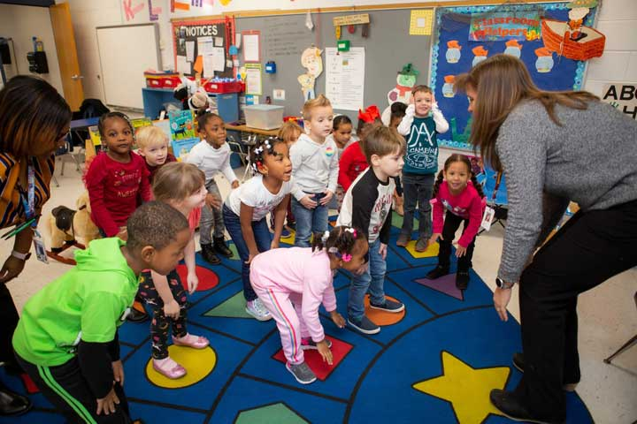 Young children moving and jumping in the classroom.