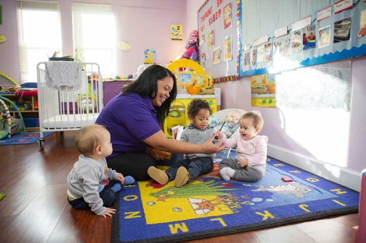 Teacher and group of toddlers sitting on a mat together