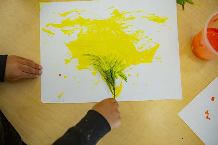 A child painting with leaves on a paper.