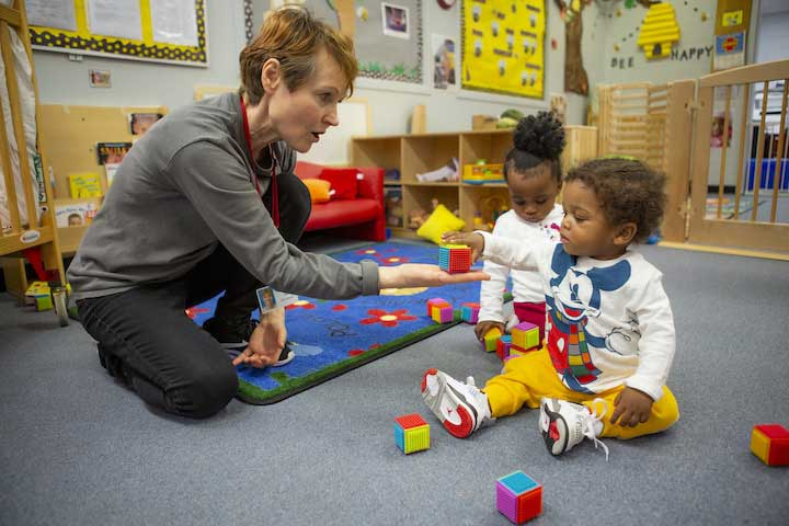 Teacher and toddlers play on carpet. Teacher holds a block in her hand as a child reaches for it