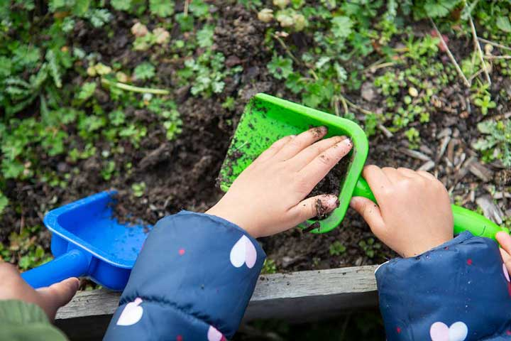 child's hands digging with a shovel in dirt