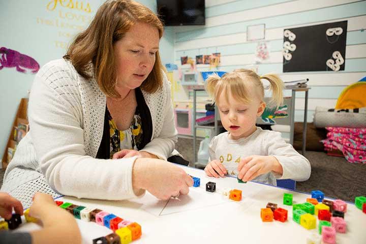 A teacher and preschooler building a triangle shape with cubes.