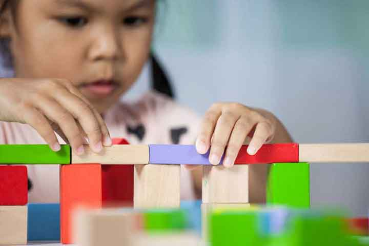 Focus on hands of cute little child girl playing with colorful wooden blocks in the room