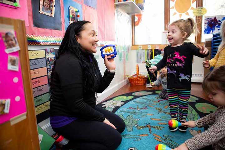 Teacher holding musical shaker with little girl dancing.